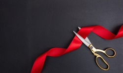Grand opening. Top view of gold scissors cutting red silk ribbon against black background, copy space