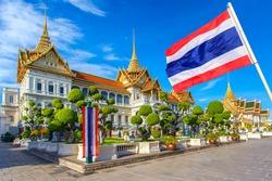 Grand palace, Wat pra kaew with blue sky and thai flag foreground, bangkok, Thailand