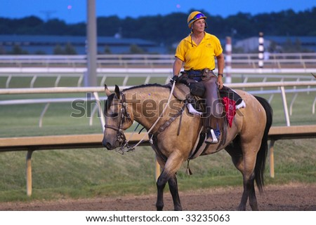 GRAND PRAIRIE,TX - JULY 4th: Trainer riding her horse at Lone Star Park Horse Race July 4th, 2009 in Grand Prairie, Texas. - stock photo