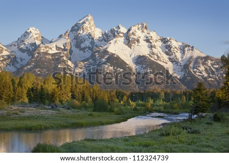 Grand Tetons range in morning light with river in foreground