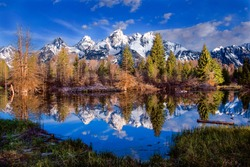 Grand Tetons reflected in a clear blue lake, early morning, in late May.