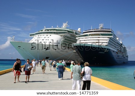 GRAND TURK, TURKS & CAICOS - JANUARY 21:  People walk along a pier near the Liberty of the Seas and The Zuiderdam ships as they lie moored January 21, 2008 in Grand Turk, Turks & Caicos.
