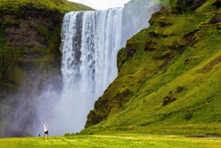 Grand waterfall Skogafoss in Iceland. Tourist in shirt and bandana threw up his hands with delight the beauty of nature