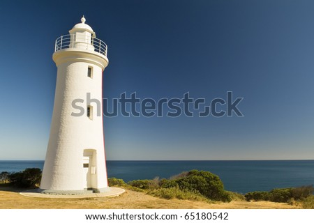 Grand white washed lighthouse looks over the deep blue ocean - stock photo