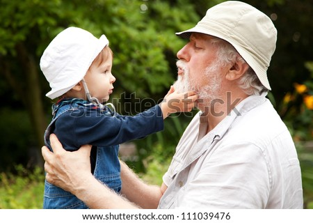 Grandchild and grandfather having fun outdoors. - stock photo