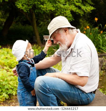 Grandchild and grandfather having fun outdoors.