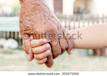 Grandchild holding grandparent for the hand,selective focus