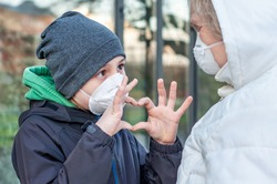 Grandchild with grandmother in respiratory mask outdoors in winter. Manifestation of feelings. Social distancing, contactless greeting. Coronavirus covid-19. Boy shows heart with his fingers. Love