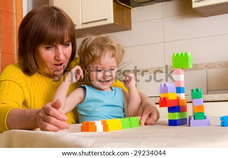 grandchild with grandmother plays cubes at home