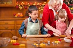 grandchildren and  grandmother baking Christmas cookies
