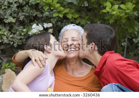 Grandchildren kissing their grandma in the garden