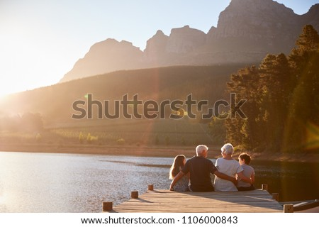 Grandchildren With Grandparents Sitting On Wooden Jetty By Lake Сток-фото ©