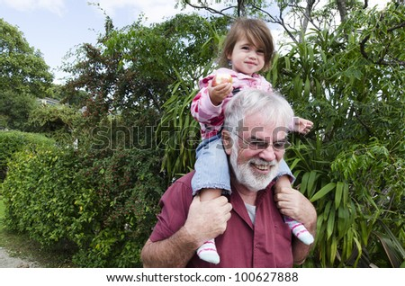 Granddad carry his grandchild on his shoulder.Concept photo of grandparents, grandfather, grandad,granddad ,grandchild, childhood, granddaughter, relationship, lifestyle,family, education.