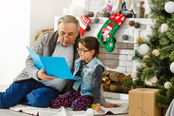 granddaughter and grandfather are sitting near the fireplace and reading