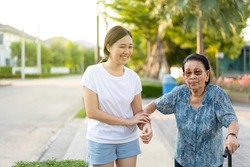 Granddaughter assist her grandmother whose age almost 90 years old exercise by walking at the park in the morning. Asian woman helping retired elder woman walking. Healthcare, wellness and wellbeing.