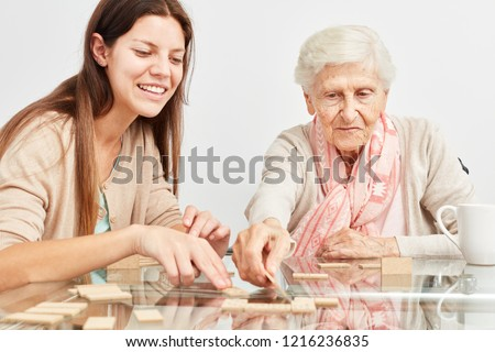 Granddaughter plays domino together with grandmother at home