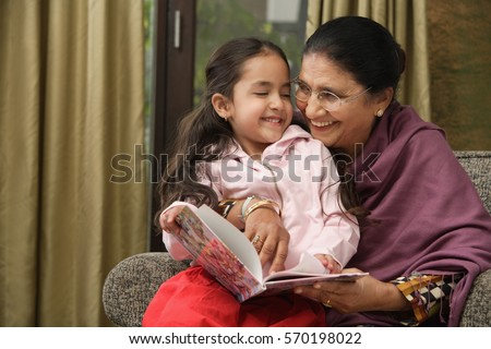 granddaughter sits on grandmother's lap for story (horizontal)