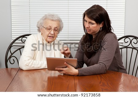 Granddaughter Teaching Grandmother How to Use a Tablet PC