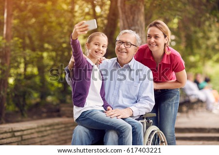 granddaughter using phone for selfie with her disabled father in wheelchair and mother in the park