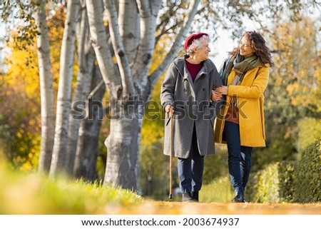 Granddaughter walking with senior woman in park wearing winter clothing. Old grandmother with walking cane walking with lovely caregiver girl. Happy woman and smiling grandma walking in autumn park.