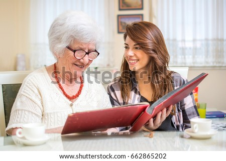 Granddaughter with her grandmother looking at photo album.