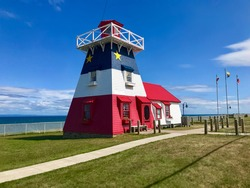 Grande-Anse Acadian LIghthouse a tourist attraction  in New Brunswick, Canada under blue skies in the summer time