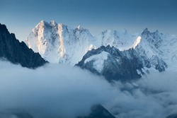 Grandes Jorasses and Mer de Glace behind the clouds. Winter season in France. First snow in Chamonix valley in Haute Savoie. Popular climbing attraction. Europe Alps summits