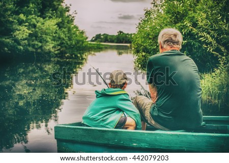 grandfather and boy fishing together. HDR. boy and an old man sitting in a boat with a fishing rod. view from the back #442079203
