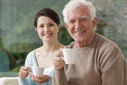 Grandfather and granddaughter are drinking tea together