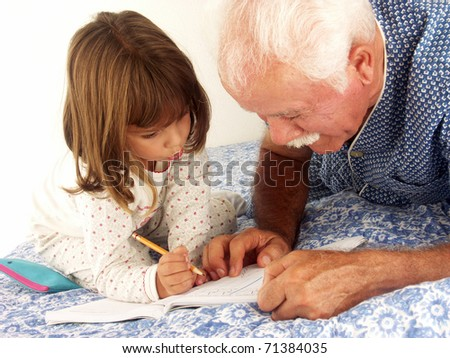 grandfather and granddaughter drawing and reading in a bed.