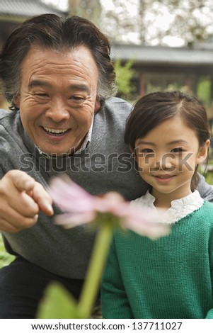 Grandfather and granddaughter looking at flower in garden
