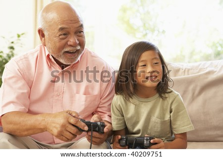 Grandfather And Granddaughter Playing Computer Game At Home