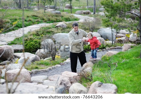 Grandfather and granddaughter walking in a spring park