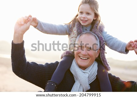 Grandfather And Granddaughter Walking On Winter Beach