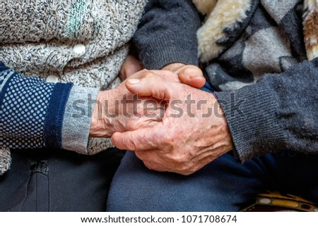 grandfather and grandmother joined hands; the manifestation of love, affection and care in old age #1071708674