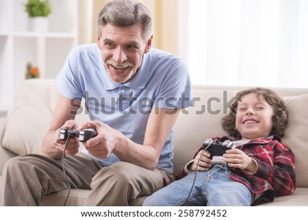 Grandfather and grandson are playing video games at home.