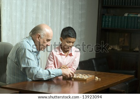 Grandfather and grandson are sitting at a table playing checkers. Grandfather is moving a piece while grandson watches. This is a horizontally framed photo.