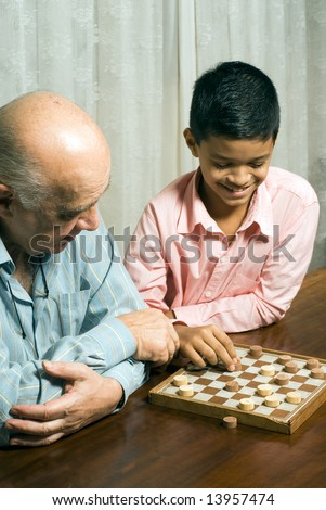 Grandfather and grandson are sitting at the table while playing a game of checkers. Grandson is moving a piece while grandfather watches. This is a vertically framed photo.