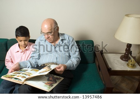 Grandfather and grandson are sitting on the couch. Grandfather is reading a book to his listening grandson. This is a horizontally framed photo.