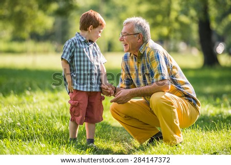 Grandfather and grandson are talking in park