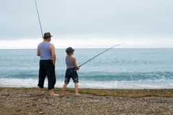 Grandfather and grandson fishing at the weekend at sea. Early in the morning.