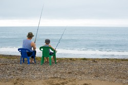 Grandfather and grandson go fishing in the sea.