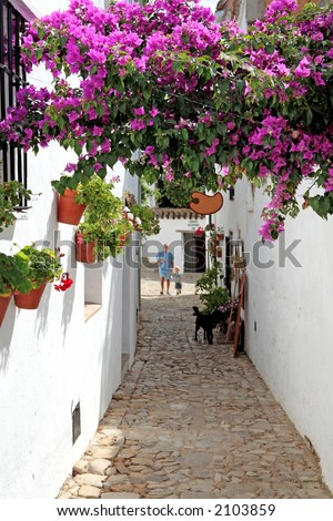 Grandfather and Grandson in narrow cobbled streets of colourful white Pueblo on vacation in Spain