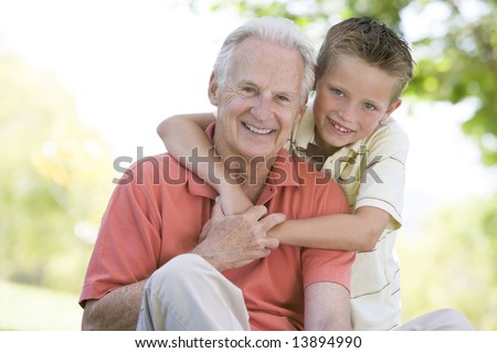 Grandfather and grandson outdoors smiling