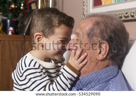 Grandfather and grandson playing and smiling at home