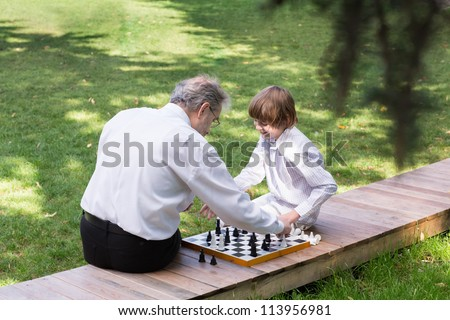 Grandfather and grandson playing chess in a park