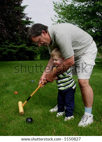 Grandfather and grandson playing croquet