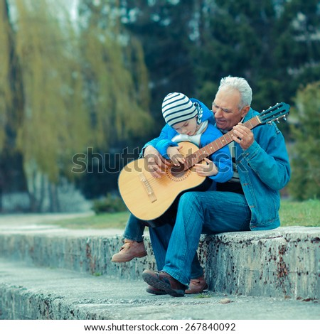 Grandfather and grandson playing guitar outdoors