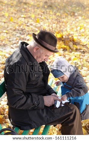 Grandfather and grandson sharing a tablet-pc surfing the internet together as they enjoy a day out in the fresh air at the park on a cold autumn day