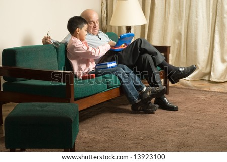Grandfather and grandson sitting on couch together playing games. Grandson plays with device on grandfathers lap.  This is horizontally framed.